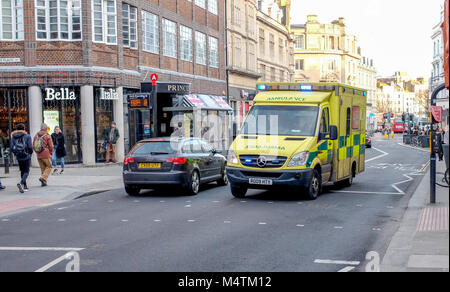 Brighton UK February 2018 - Emergency Services SECAMB ambulance driving through city with siren and blue lights - Stock Photo