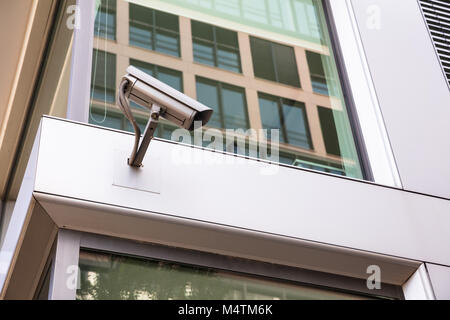 Low angle view of security camera mounted on office building in city - Stock Photo