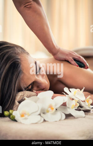 Woman enjoying the therapeutic effects of a traditional hot stone massage - Stock Photo