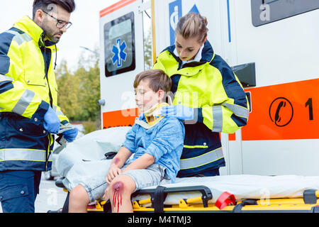 Emergency medics taking care of injured boy - Stock Photo