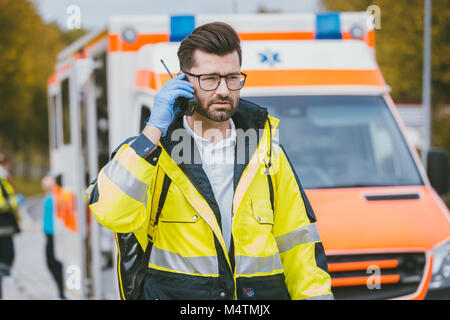 Medic talking to headquarter via radio in front of ambulance - Stock Photo