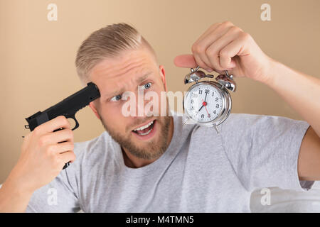 Close-up Of A Angry Young Man Holding Gun And Alarm Clock - Stock Photo