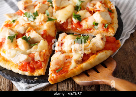 Hot sliced buffalo pizza with chicken, tomatoes and cheese macro on the table. horizontal - Stock Photo