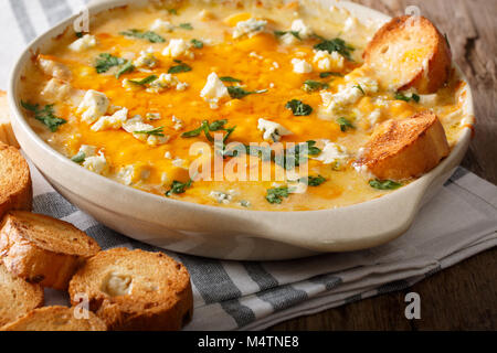 Homemade hot buffalo chicken dip with crostini close up in baking dish on the table. horizontal - Stock Photo