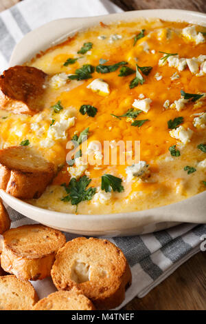 Hot buffalo dip with chicken and crostini macro in a dish on the table. vertical - Stock Photo