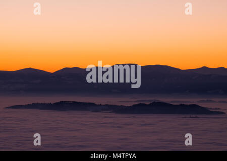 View from mountain Schoeckl over low stratus to mountain range Pack with Speikkogel and Ameringkogel to sunset - Stock Photo