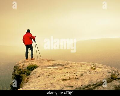 Professional photographer on location takes photos with mirror camera on peak of rock. Dreamy foggy landscape, spring - Stock Photo