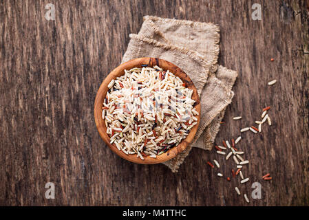 Mix of brown, red and wild rice in bowl - Stock Photo
