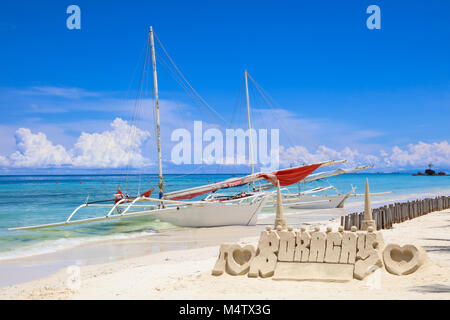 Sand castle in a shape of I LOVE BORACAY and local fishing boats on White Beach, Boracay Island, Philippines. Tropical - Stock Photo