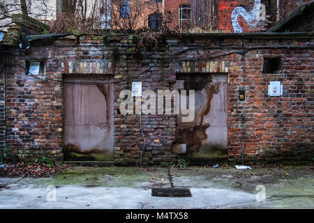 Berlin,Mitte. Urban decay, weathered old brick wall and totting wooden doors in courtyard of building - Stock Photo