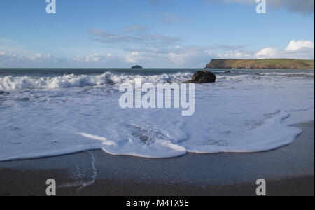 White water with crashing waves at a rocky and sandy beach at Cornwall. - Stock Photo