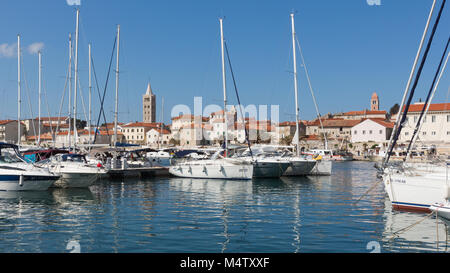 View from Rab marina on Rab old town with towers and sailing yachts - Stock Photo