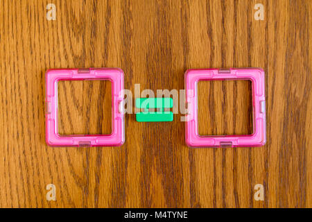 Two red squares and a sign are equal on a wooden background. Geometrical finishes. - Stock Photo