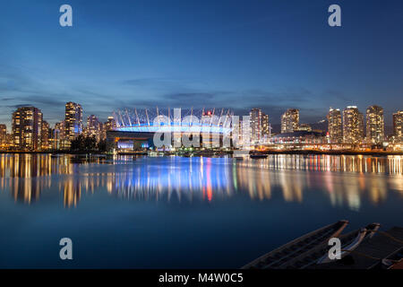 BC Place and the condos of False Creek reflecting in the water of False Creek. Taken at sunrise looking north from - Stock Photo
