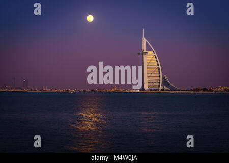 Dubai, UAE, December 13, 2016: full moon is rising over Burj Al Arab - the world's only 7-star luxury hotel - Stock Photo