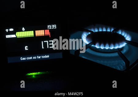 Chameleon Technology Smart meter showing cost of gas used today with gas hob in the background, England, UK - Stock Photo