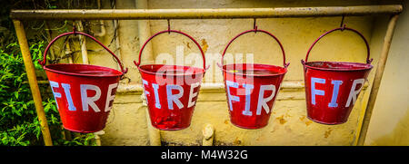 A row of four red buckets labelled 'Fire' in white letters for collecting water to douse a fire set against yellow - Stock Photo
