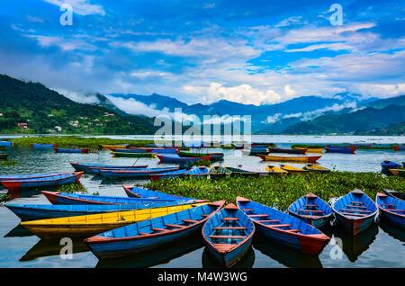 Colorful row boats docked on Lake Phewa in Pokhara, Nepal. - Stock Photo