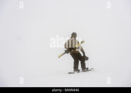 A skier carries part of the equipment of an injured companion on the slopes of the ski resort of Sierra de Béjar - Stock Photo