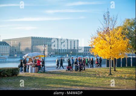 People enjoy a Sunday walk at Skeppsholmen during fall in Stockholm. The Royal Palace visible in the background. - Stock Photo