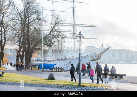 People enjoy a Sunday walk during autumn at Skeppsholmen island in Stockholm. The capital city of Sweden is built - Stock Photo