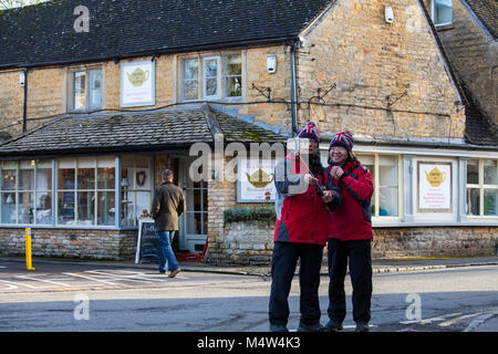 BOURTON ON THE WATER, UK - FEBRUARY 15th, 2018: Tourists are taking pictures in Bourton-on-the-Water, which  is - Stock Photo