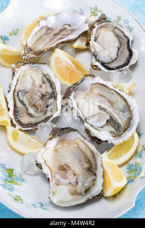 Plate with raw oysters and lemon slices on ice. - Stock Photo