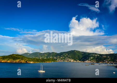 Charlotte Amalie, St. Thomas, USVI. Sailboat and hills of waterfront harbor with rainbow peaking through clouds - Stock Photo