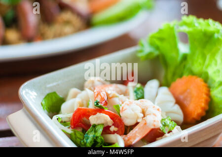 Prawn and squid spicy salad on dish wood background, Thai traditional mix seafood - Stock Photo