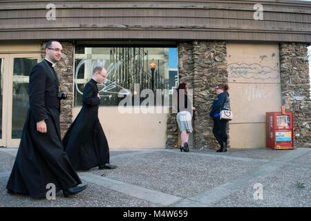 Two women chat in Sacramento while priests walk down the street. - Stock Photo