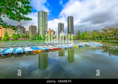 Pedal boats and Tokyo skyscrapers reflecting on Shinobazu Pond in Ueno Park, a public park next to Ueno Station - Stock Photo