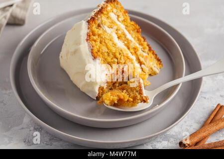 Piece of carrot homemade cake with white cream on a gray background. Festive dessert concept. - Stock Photo
