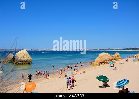 Tourists relaxing on the beach with large rocks and views across the ocean towards the coastline, Praia da Rocha, - Stock Photo