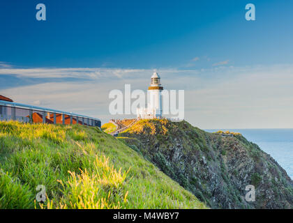 Byron Bay Lighthouse resplendent as the sun sets over the Northern New South Wales coastal community, lots of people - Stock Photo