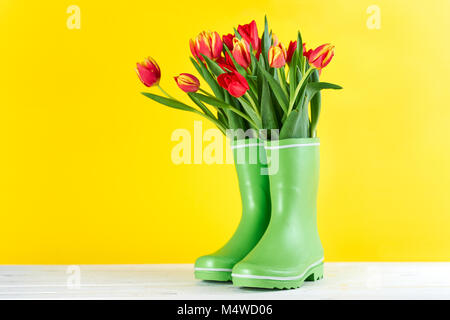 Red tulips in rubber boots - Stock Photo