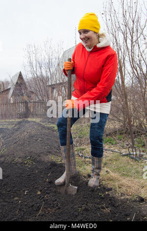 Happy young woman farmer digging with a shovel in his garden - Stock Photo