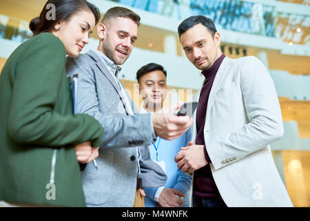 Low angle portrait of modern businessman holding smartphone showing something to group of colleagues standing in - Stock Photo