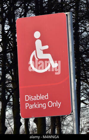 A red and highly noticeable conspicuous disabled parking only sign in a large supermarket or hypermarket car park. - Stock Photo