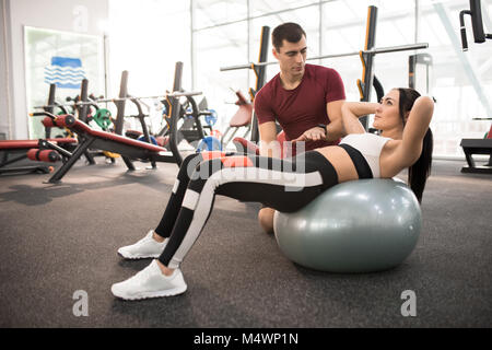Side view portrait of muscular coach helping young woman doing exercises on fitness ball  in modern gym, copy space - Stock Photo