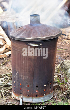 A garden dustbin type or style incinerator or bonfire contained within a galvanised steel dustbin smoking heavily - Stock Photo