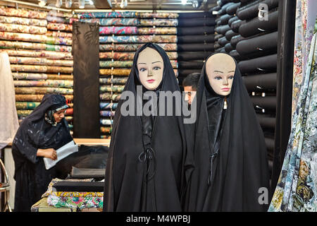 Tehran, Iran - April 29, 2017: Two mannequins dressed in black Islamic clothes, a religious veil of a chador, in - Stock Photo