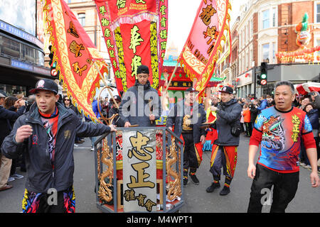 Chinese drummers accompanying the Chinese New Year parade, near Chinatown, London, England, United Kingdom.  Crowds - Stock Photo