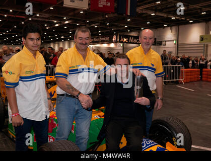 Nigel Mansell CBE, surrounded by the Benetton F1 Team Mechanics,  posing with the London Classic Car Show 'Icon' - Stock Photo