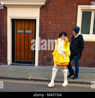 Colour Photograph of a girl in the yellow dress in Soho, London, England, UK. Credit:London Snapper - Stock Photo