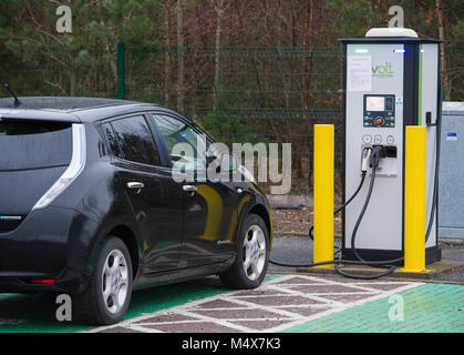 A Nissan Leaf electric car using a tri-rapid charger at a electric vehicle charging station, Riccarton, Edinburgh. - Stock Photo