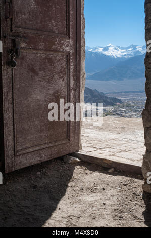 A view of the Zanscar mountain range, through an open door, overlooking Leh, Ladakh. India. - Stock Photo