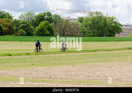 A couple cycling on narrow path through fields at Prévessin Moëns, France - Stock Photo