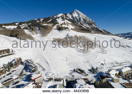 The Crested Butte, Colorado Mountain Resort ski area base and ski lifts from a drone on a perfect winter afternoon. - Stock Photo