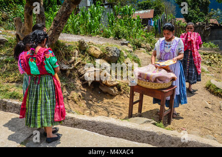 School children at a rural school in Guatemala gather coins to purchase lunch from a street vendor. - Stock Photo
