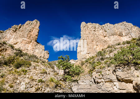 Keyhole opening to vivid blue sky in canyon cliffs on Devil's Hall trail at Guadalupe Mountains National Park in - Stock Photo
